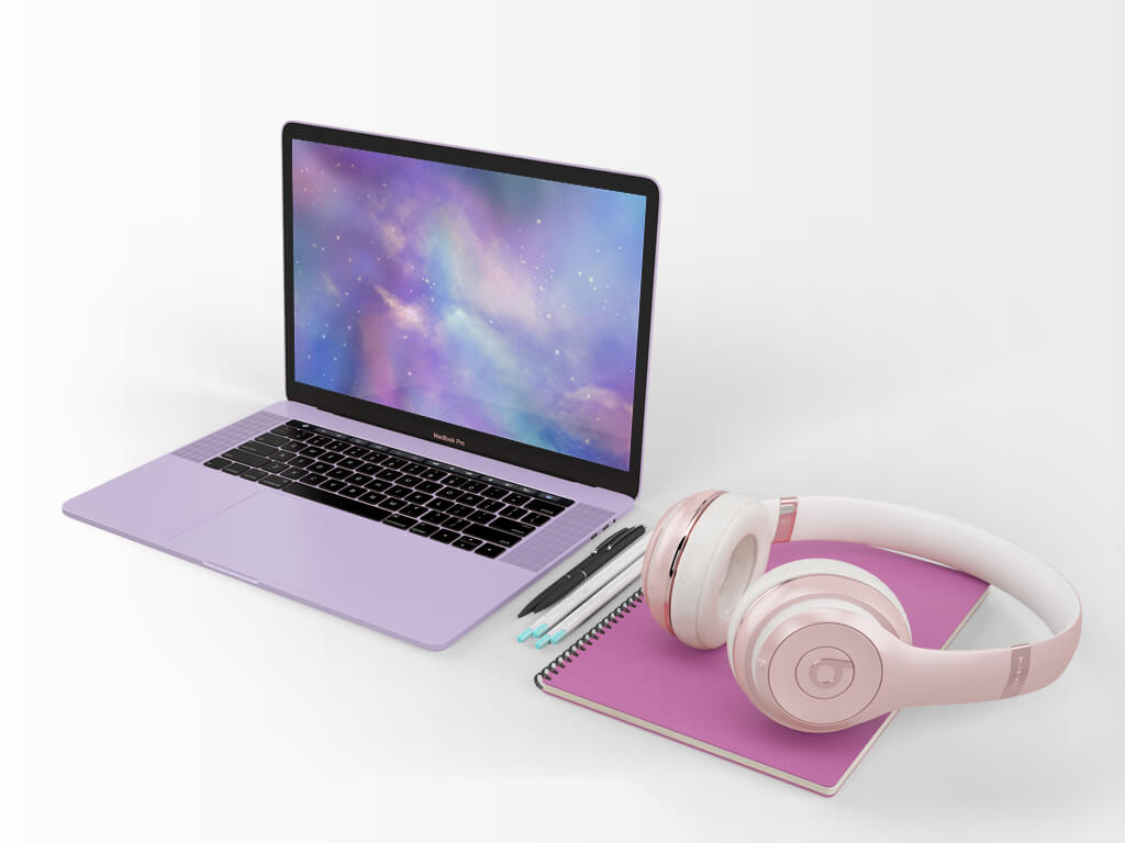 purple laptop with ethereal galaxy picture displayed beside rose gold headphones on a pink notebook - custom website design